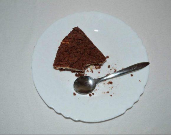 Čokoládový koláč s odštiknutým kúskom spolu s lyžičkou